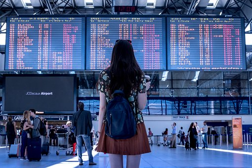 Photo of a woman looking a screen denoting flight times at an airport.