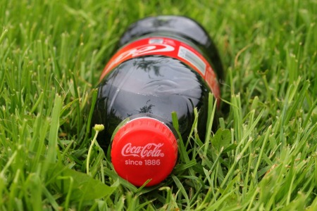 Photograph of a full bottle of Coca Cola laying in the grass.