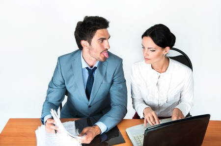 Photo of men looking at woman making a silly face. She looks serious. Both in professional attire, at work.