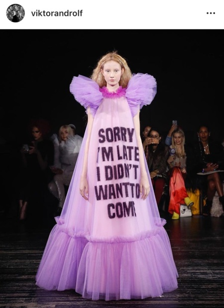 """Image of a dress in a fashion show which has the following words """"SORRY I AM LATE, I DID NOT WANT TO COME"""""""