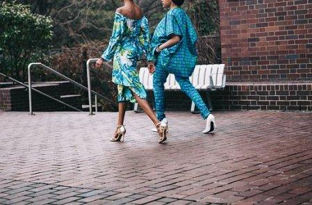 Two women fashionably dressed women walk across a brick patio.