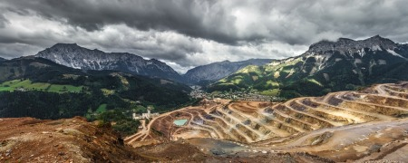 Photo of a mining pit, with a mountain range in the background.