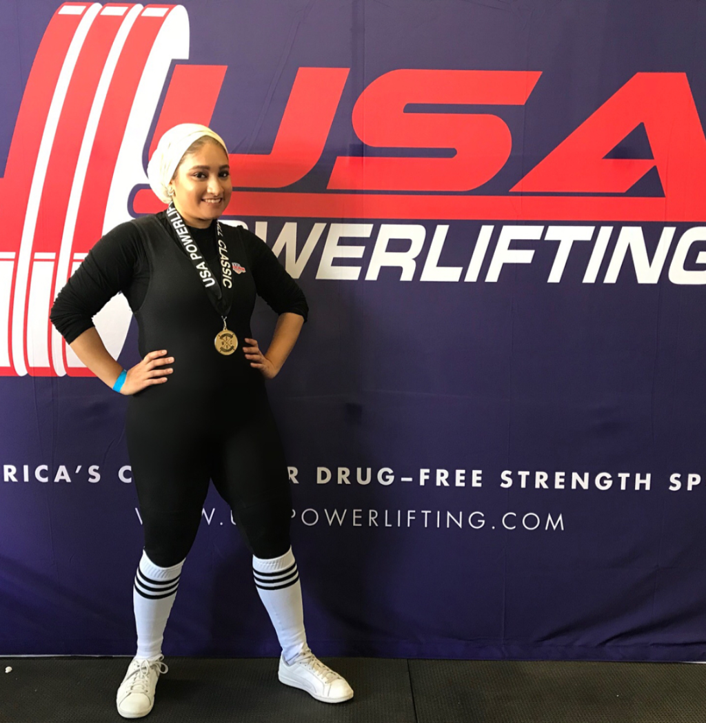 Photo of female athlete wearing a hijab and a medal