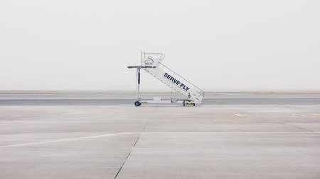 Photo of an airplane staircase without a plane nearby, on a foggy day.