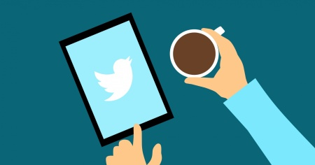 Graphic of a tablet with the twitter logo on the screen, on a table. The person using the tablet is also holding a coffee mug.