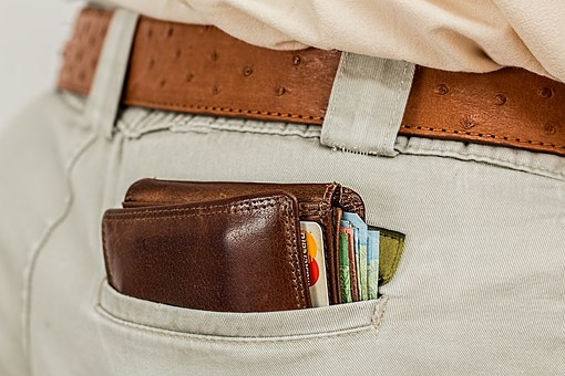 Close up photo of a wallet peeking out of a man's back pocket. He's dressed business casual.