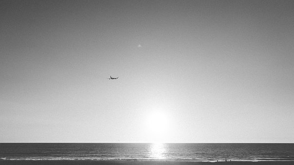 Black and white photograph of a distant plane flying over the ocean.