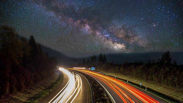 Photo of a time lapse photo showing the milkyway galaxy, and busy highway at night.