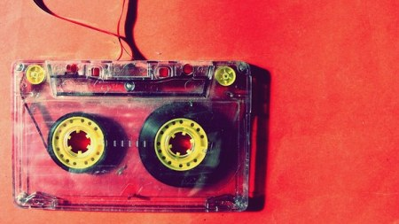 Photo of a partially unspooled cassette tape on a red background,