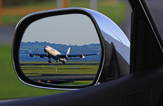 Photo of a grounded aircraft, reflected in the sideview mirror of a car.