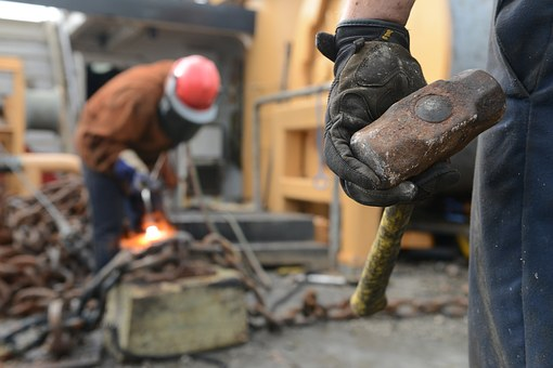 Photo of construction workers laboring. A sledge hammer in the foreground, a man welding in the background.